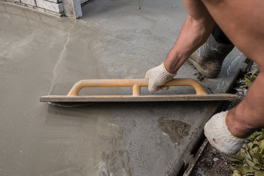man putting concrete on the floor